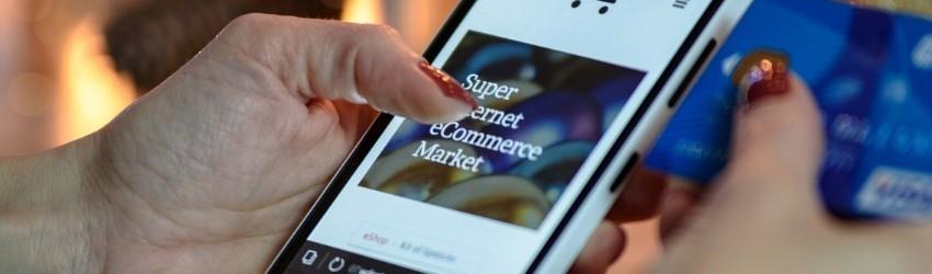 UE nuove regole digitali: donna che fa acquisti dal proprio smartphone su un e-commerce con la carta di credito alla mano